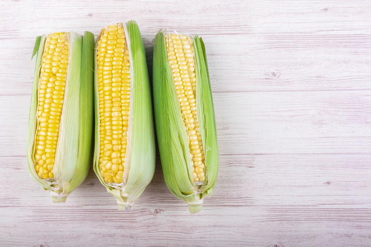 fresh raw sweet corn on the cob kernels over wooden background Food And Drink Vegetable Food Table Still Life Freshness Corn Wellbeing Wood - Material Healthy Eating Indoors  High Angle View Directly Above Close-up No People Sweetcorn Green Color Corn On The Cob Raw Food Group Of Objects Vegetarian Food