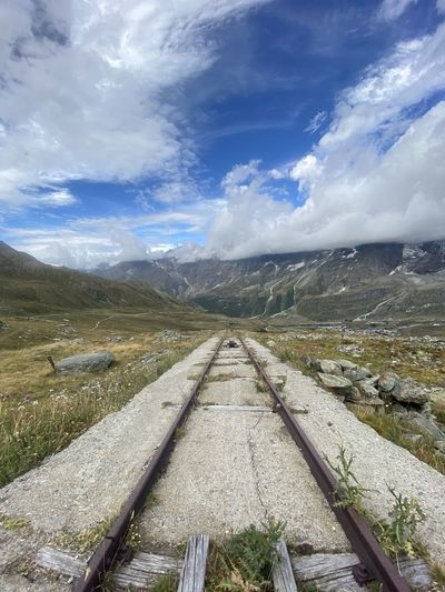 Railroad track leading towards mountains against sky