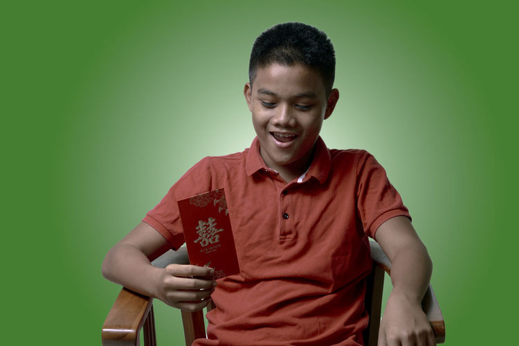 Smiling Boy Holding Envelop While Sitting On Chair Against Green Background