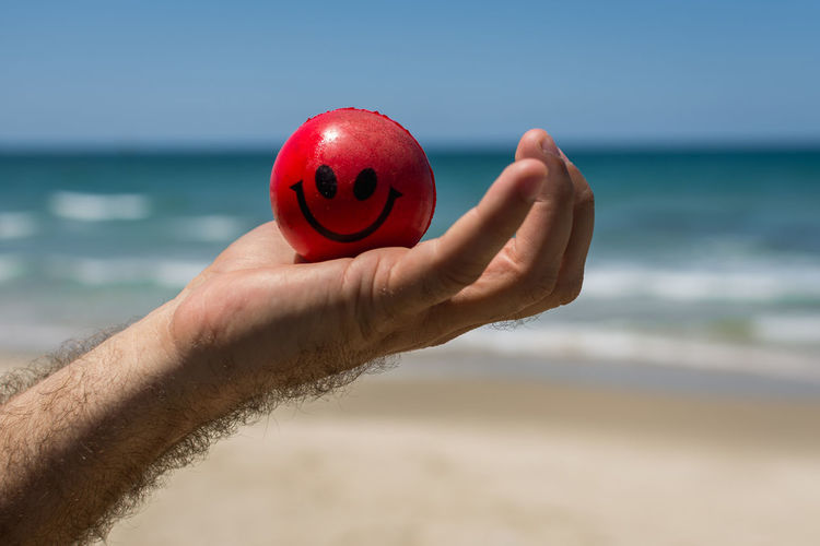 Close-Up Of Hand Holding Red Ball Against Beach