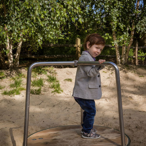 Side view of cute boy standing on merry-go-round at playground