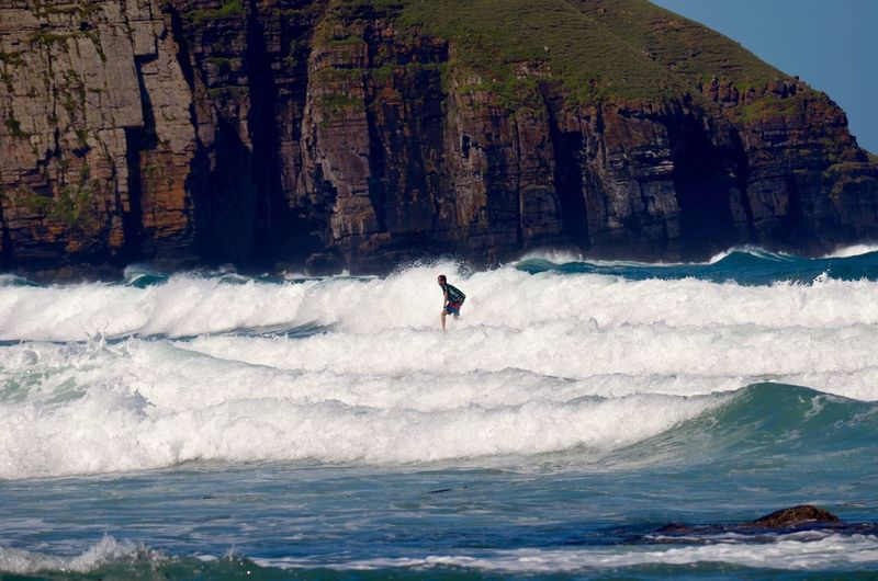 Man surfboarding on sea waves by cliff
