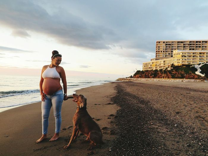 Full length of pregnant woman with dog on beach against sky