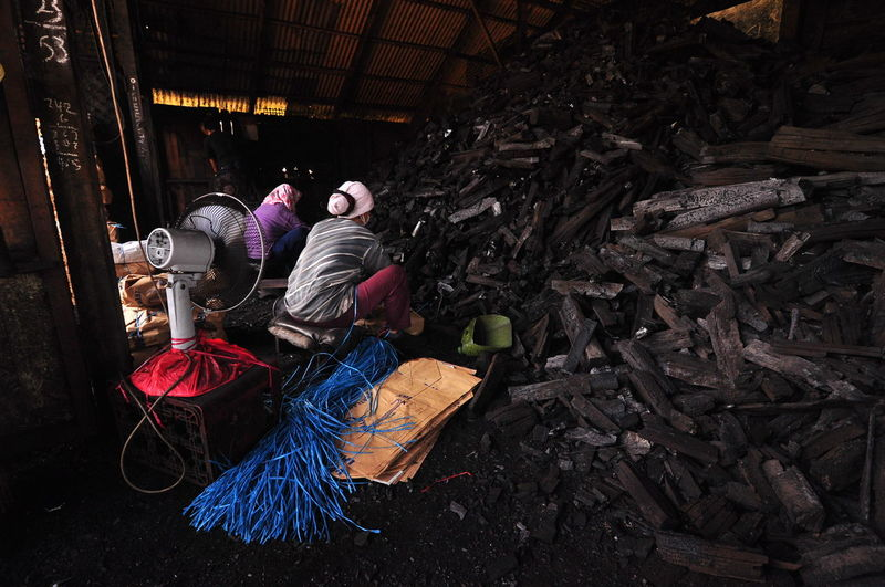 Mangrove Charcoal at the local charcoal factory in Kuala Sepetang, Malaysia Black Background Perak Raw Smoke Stove Taiping Wood Black Charcoal Background Charcoal Charcoal Factory Day Factory Manual Worker Occupation Old Outdoors Packing Pattern People Real People Surface Texture Traditional Village Working First Eyeem Photo