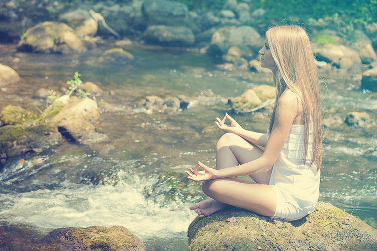 Side view of young woman meditating on rock in river