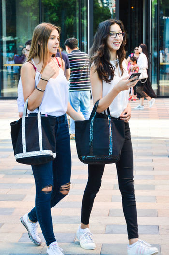 Building Exterior Casual Clothing City Day Friendship Full Length Happiness Leisure Activity Lifestyles Outdoors People Purse Real People Sidewalk Smiling Street Togetherness Walking Young Adult Young Women