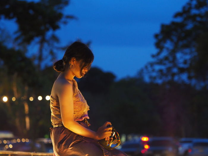Side view of woman against sky at night