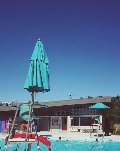 Lifeguard hut in sea against clear blue sky
