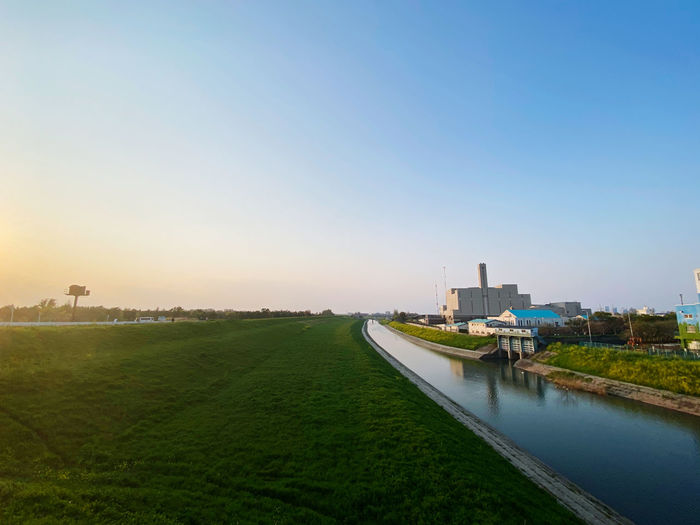 Scenic view of canal amidst field against clear sky