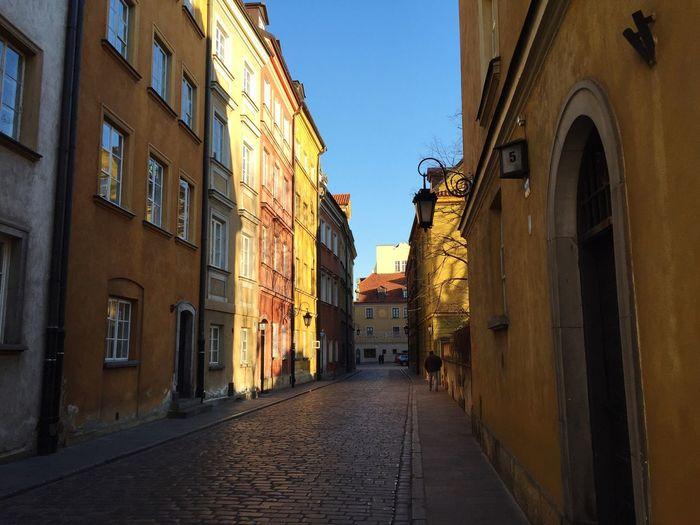 Empty narrow road along buildings