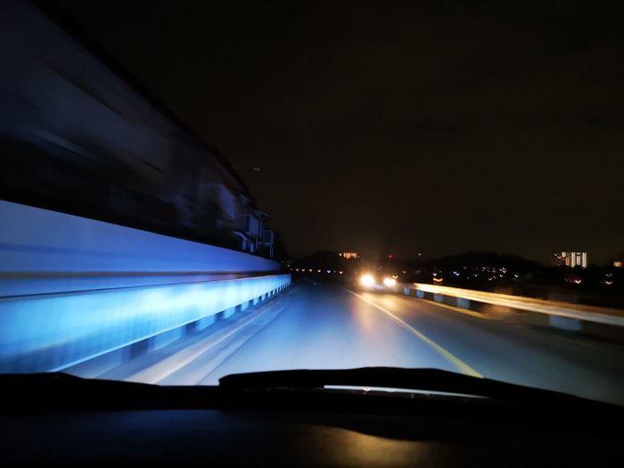 Illuminated car on road seen through windshield