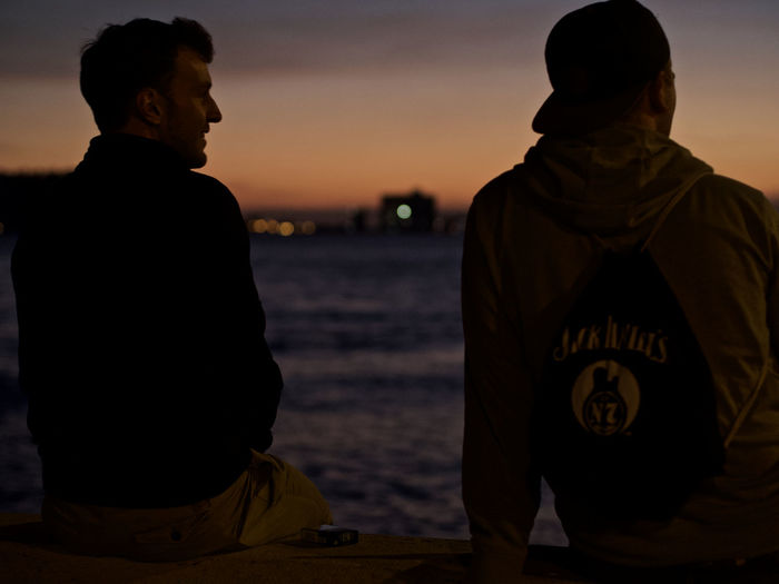 Men Real People Sky Sunset Rear View Two People Water People Lifestyles Nature Waist Up Standing Sitting Togetherness Leisure Activity Beach Text Sea Bonding Adult