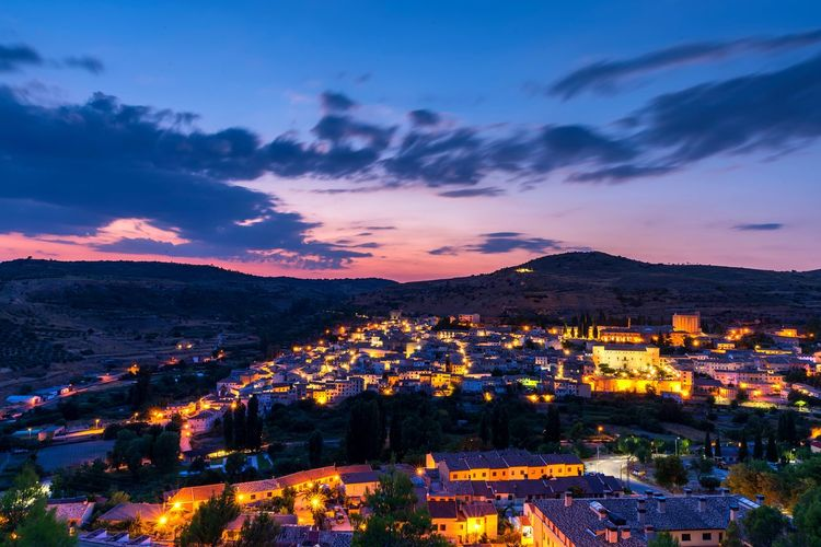 High angle shot of illuminated townscape against sky at sunset