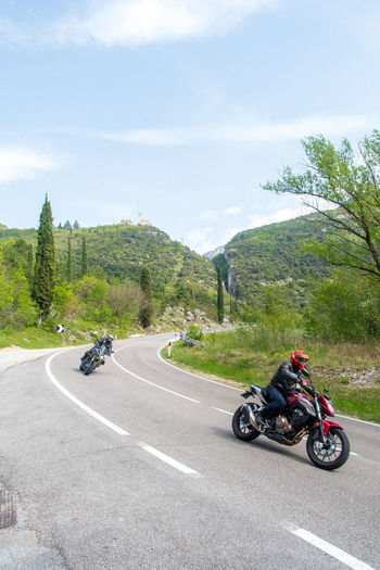Motorcycle on road by mountain against sky