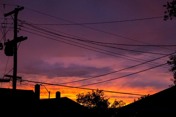 Low angle view of silhouette electricity pylon against sky