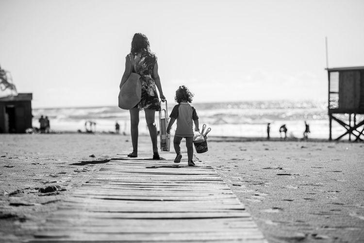 Rear view of people walking on boardwalk at beach against sky