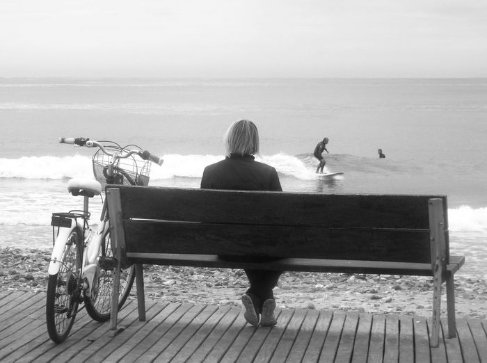 Rear View Of Woman Sitting On Bench While Looking At Man Surfing On Sea