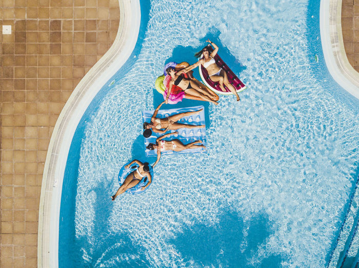 Directly above shot of people relaxing in swimming pool