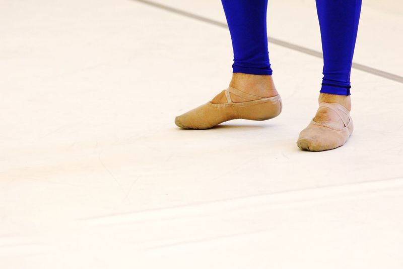 Low Section Of Male Ballet Dancer Standing On Floor