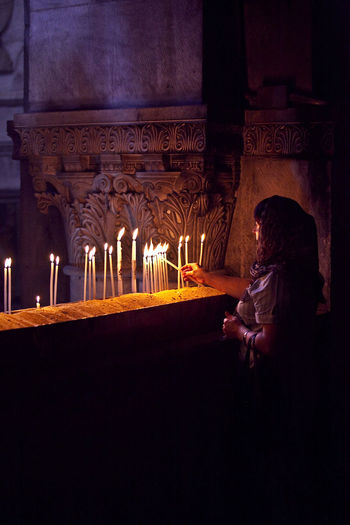 Lighting candles at the Church of the Holy Sepulchre Candles Casual Clothing Christianity Church Dark Holy Holy Places Holy Sepulchre Holyland Illuminated Lighting Candles Night Place Of Worship Religion Religious  Side View Spirituality Temple - Building