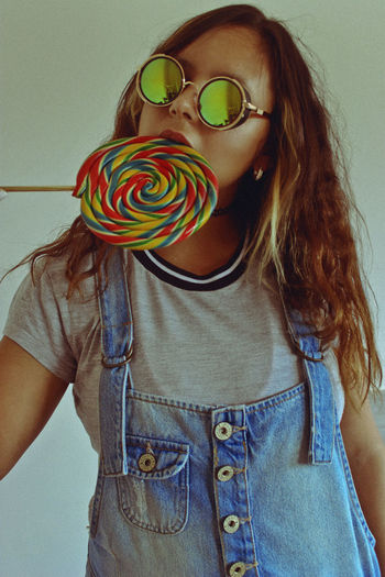 Young Woman Eating Lollipop While Standing Against Wall