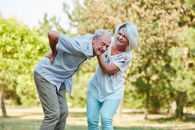 Mature Woman Holding Senior Man Suffering From Backache In Park
