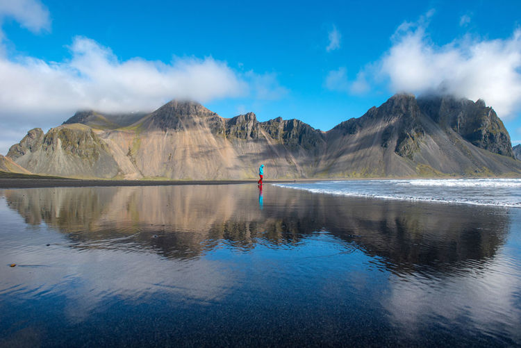 Person standing on beach against mountain