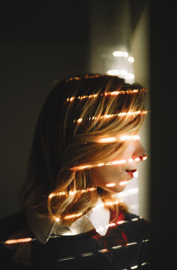 Portrait Of Woman Standing By Blinds With Sunlight On Face