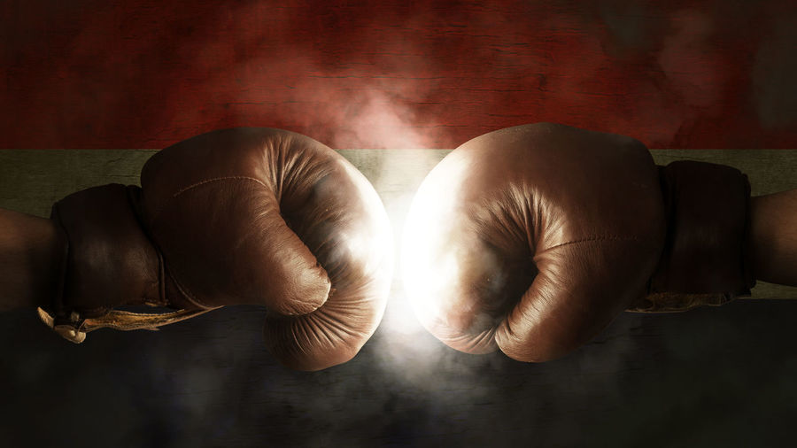 Cropped image of boxers fighting against illuminated croatian flag