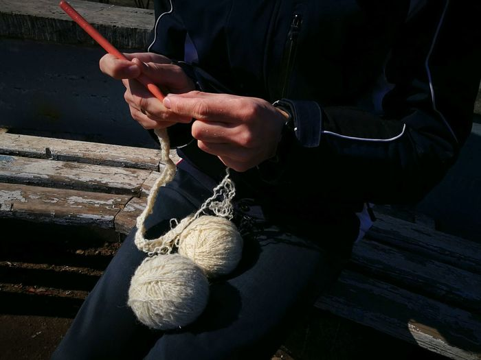 Midsection Of Woman Holding Wool Balls On Bench