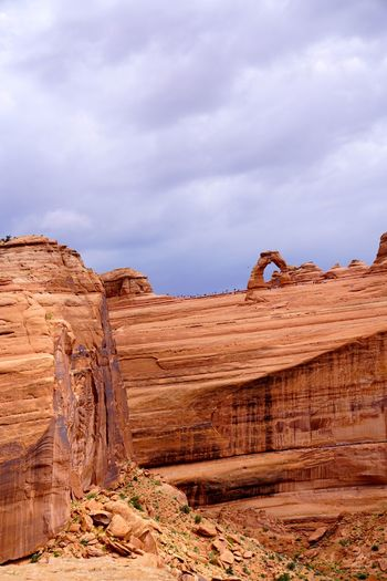 Rock formations against cloudy sky