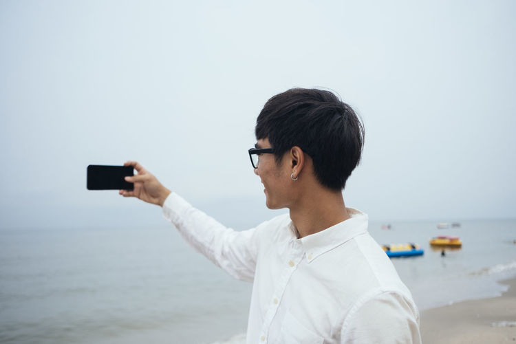 Portrait of man photographing with mobile phone at beach