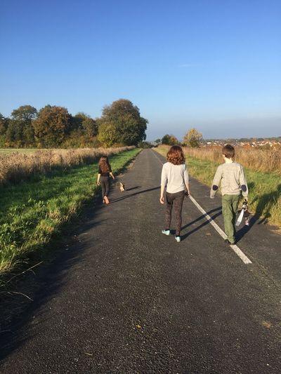 Rear view of siblings walking on country road against sky