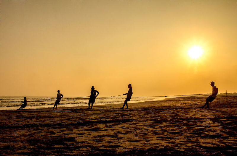 Silhouette people playing at beach against clear sky during sunset