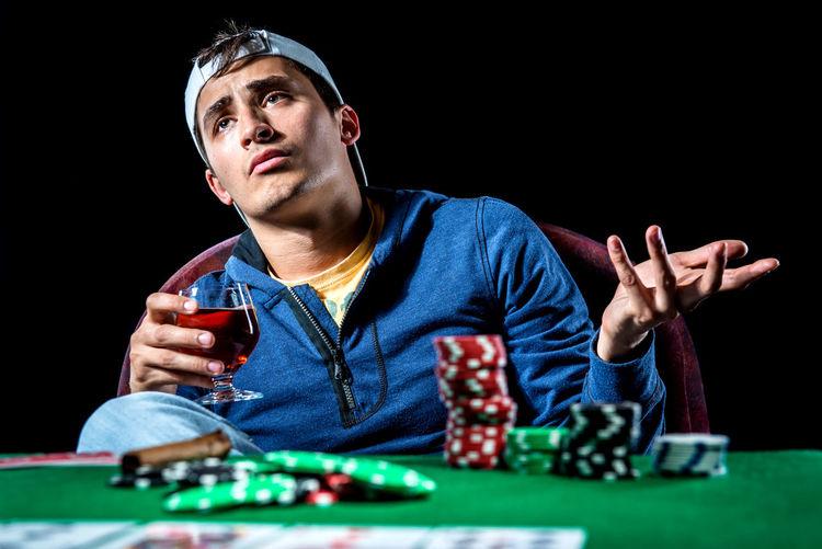 Poker player. Gambling concept Blackjack Casino Gambling Jackpot Man Poker Addiction Casino Night Entertainment Gambler Gambling Gambling Chip Game Leisure Games Male One Person Player Playing Playing Card Games Poker - Card Game Poker Chips Poker Game Studio Shot Table Young Adult