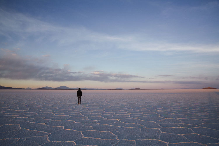 Arid Climate Beauty In Nature Bolivia Cloud - Sky Desert Horizon Over Land Landscape Nature One Person Outdoors People Real People Salt - Mineral Salt Basin Salt Flat Scenics Sky Standing Tranquil Scene Tranquility Travel Destinations Uyuni Salt Flat