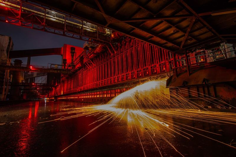 Man spinning wire wool at factory during night