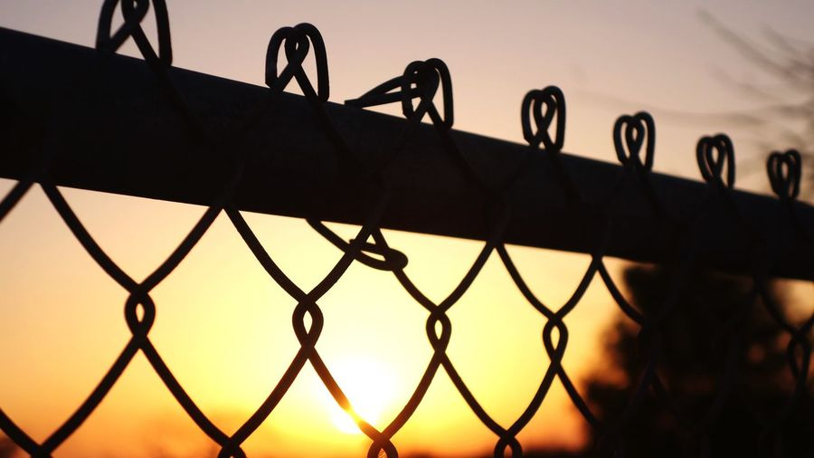 Close-up of chainlink fence against sky during sunset