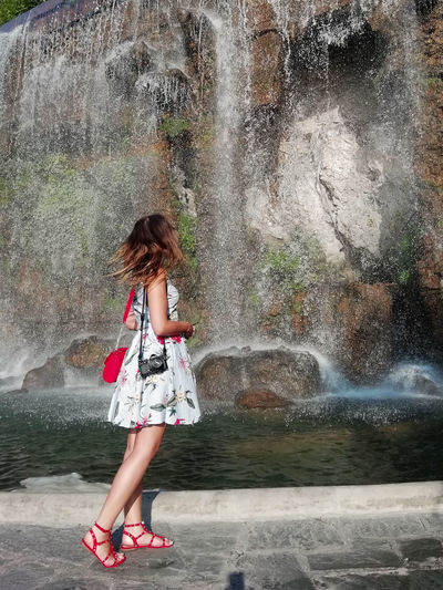 Full length of woman in water fountain