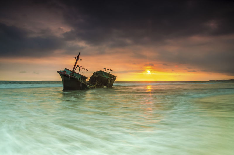 The Old Shipwreck Skyscraper Sunset_collection Seascape Beachphotography Landscape_photography Shipwreck Yellow Sunset Motion Capture Waves, Ocean, Nature Long Exposure Nikonphotography Indonesia Photography  Wallpaper Background WallpaperForMobile