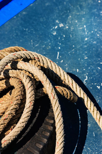 High angle view of rope and tire on boat deck