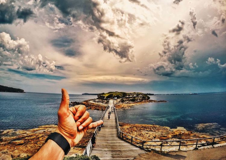 Cropped image of man gesturing shaka sign against footbridge on sea