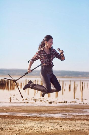 Beautiful Singer Jumping With Microphone Stand On Field Against Sky