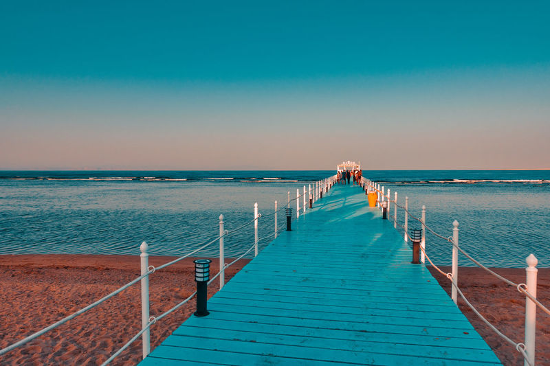 RIXOS SHARM EL SHEIK, EGYPT - AUGUST 25, 2015: Pier into the blue sea with tourists Sea Water Sky Horizon Over Water Horizon Clear Sky Scenics - Nature Blue Railing Beach Nature Tranquility The Way Forward Tranquil Scene Beauty In Nature Direction Land Pier No People Diminishing Perspective Outdoors Long