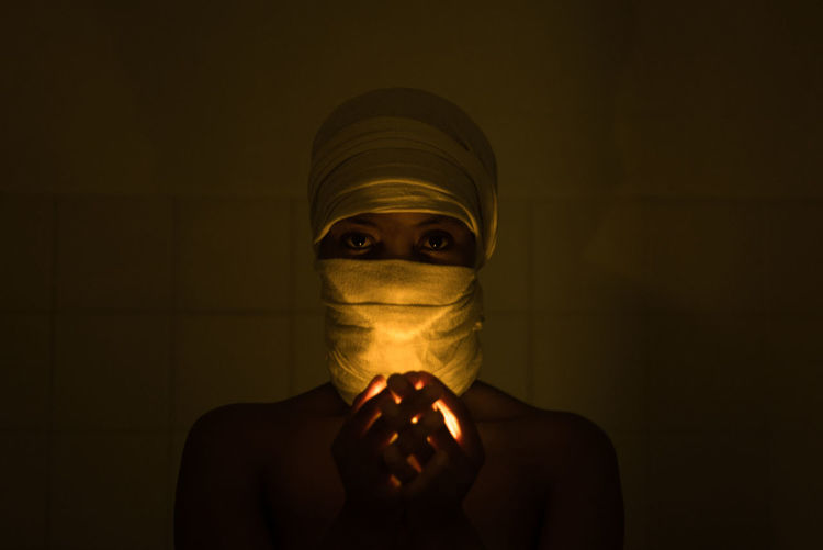 Close-up portrait of woman with covered face holding illuminated light in darkroom