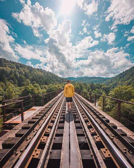 Rear view of man walking on railroad track against sky