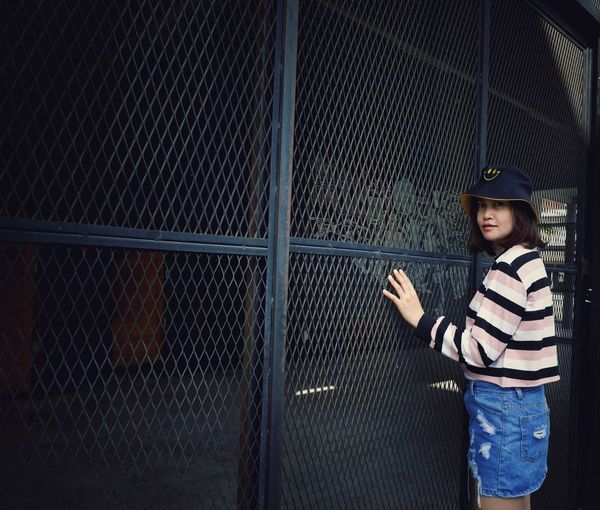 Portrait of girl standing against fence