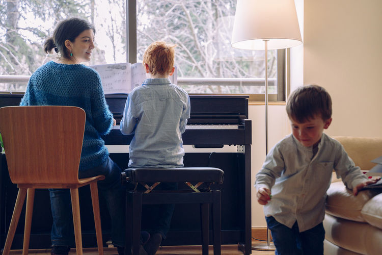 Mother and son playing piano by sibling at home