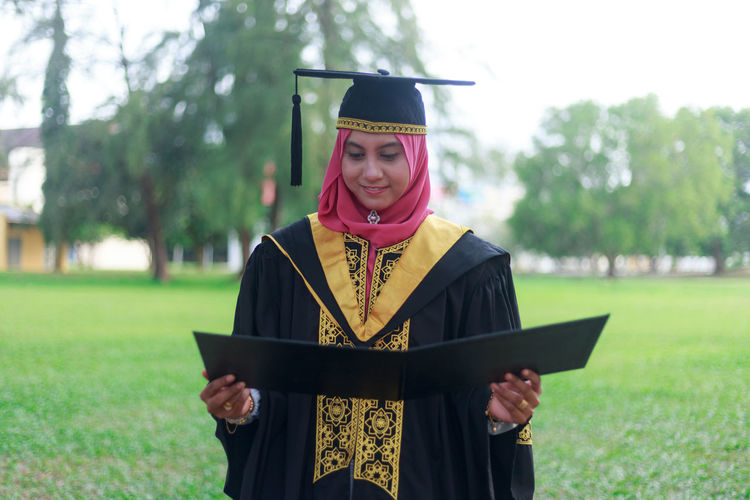 Woman in graduation gown standing on field