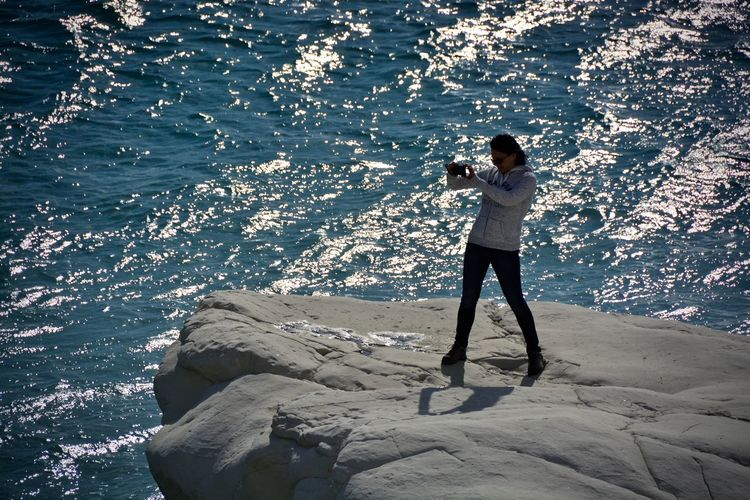 Woman standing on rocks at seaside